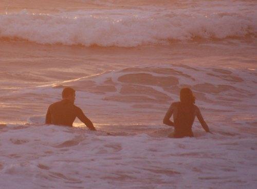 Surfers watching sunset