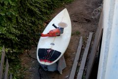 Look at the ghetto set up I have going here. My board is propped up by a cooler in the ally way on the side of my building. I like to call what I do no guerrilla surf board repair.